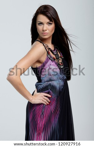 Fashionable lady in black dress posing on gray background #120927916