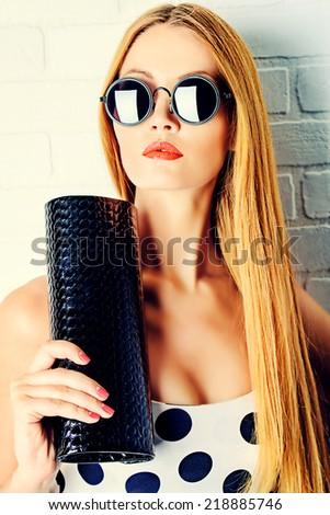 Fashionable lady near white brick wall. Beauty, fashion concept. Optics.