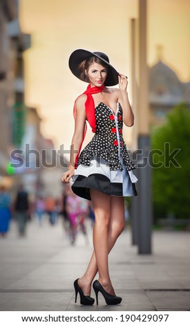 Fashionable lady wearing elegant dress, black hat and red scarf posing outdoor in urban scenery. Full length portrait of young beautiful elegant woman posing in summer city style. Street shot.
