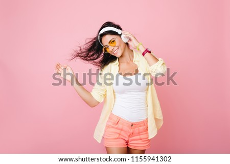 Fashionable latin girl in good mood posing for photo and dancing. Enthusiastic hispanic young lady in summer outfit relaxing while listening favorite song. #1155941302
