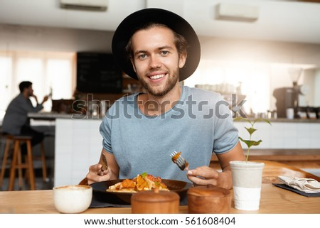 Fashionable male with beard appeasing hunger while dining alone at modern restaurant on sunny day, eating meal with knife and fork, sitting against blurred interior background and smiling happily