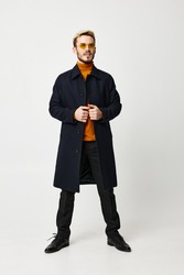 fashionable man in a dark coat spread his legs shoulder-width apart on a light background and an orange sweater model