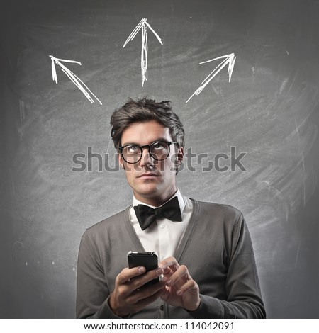 Fashionable man thinking while using a mobile phone - stock photo