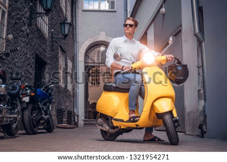 Fashionable man wearing sunglasses riding on vintage Italian scooter in the old narrow street of Europe