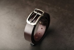 Fashionable men's brown belt made of genuine leather with a light metal buckle on a dark background. Genuine leather, handmade