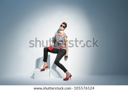 fashionable model in sunglasses on the wooden cube.