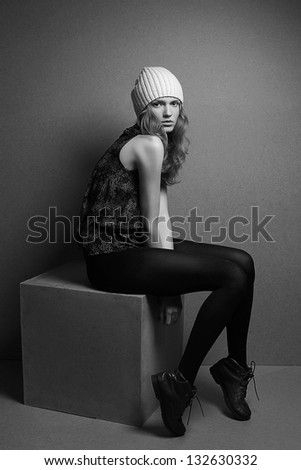 fashionable model with curly blond hair and white hat sitting on a wooden cube over wooden background. black and white (monochrome) studio shot