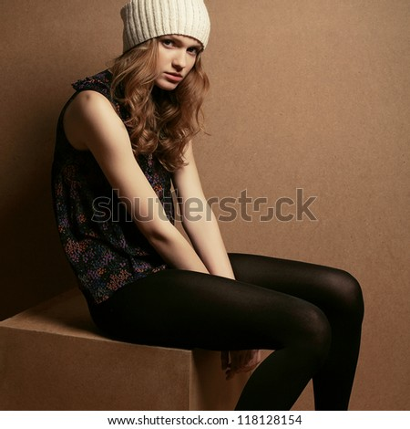 fashionable model with curly red hair and beige hat sitting on a wooden cube over wooden background. studio shot