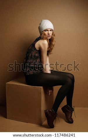 fashionable model with curly red hair and white hat sitting on a wooden cube over wooden background. studio shot