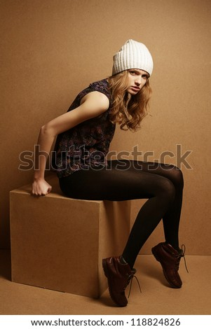 fashionable model with curly red hair and white hat sitting on a wooden cube over wooden background. studio shot - stock photo