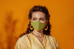 Fashionable model, woman wearing trendy outfit with protective face mask, stylish yellow earrings, chain necklace. Summer fashion during quarantine of coronavirus outbreak. Copy, empty space for text