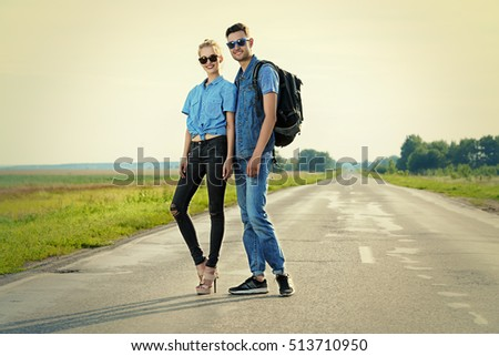 Fashionable models wearing jeans clothes posing on a highway. Denim style.