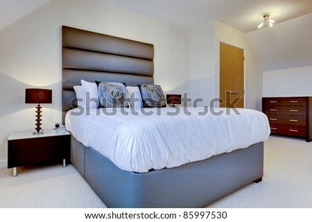 Fashionable modern bedroom simply dressed including bed with oversize headboard, lamp and cushions