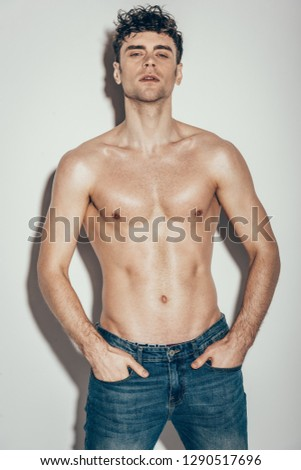 fashionable muscular man in jeans posing on grey