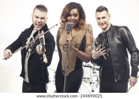 Fashionable music band posing on white background. Two handsome man and beautiful sexy woman with music instruments