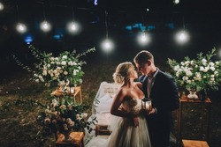 Fashionable newlyweds stand at night against the backdrop of chic decorations and flowers,electric bulbs and garlands, in the backlight. Night shooting of bride and groom.Floristics. Grain,film effect