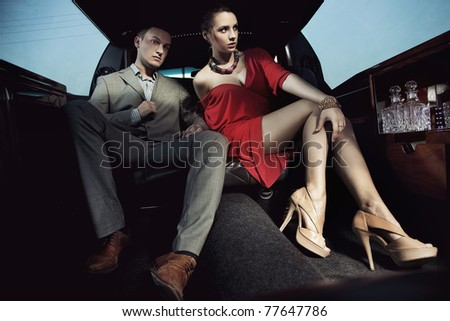 Fashionable pair in a luxury limousine