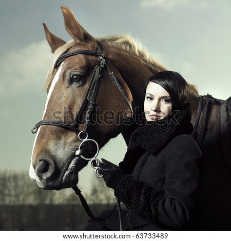 Fashionable portrait of a beautiful young woman and horse