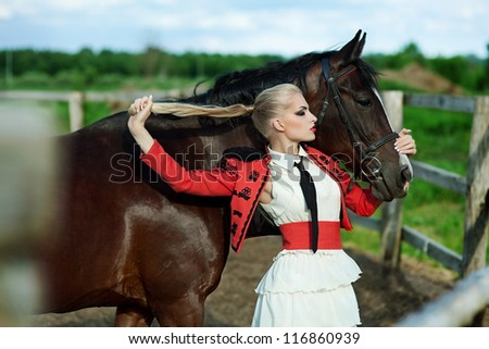 Fashionable portrait of a beautiful young woman whis broune horse