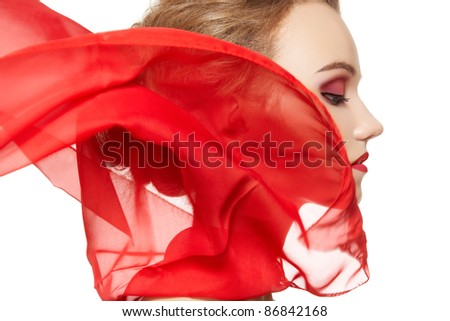 Fashionable portrait of a girl model with waving red silk scarf. Fashion, glamour accessories, evening makeup. Freedom vamp bright style, lady in red on white background