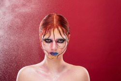 Fashionable portrait of a girl with bright color makeup. Girl on a red background and water splashes on her, drops fall on her skin, bright lips and eyes