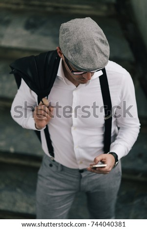 Fashionable retro dressed man with cap, suspenders and eyeglasses standing on city street and using smart phone. High angle view. #744040381