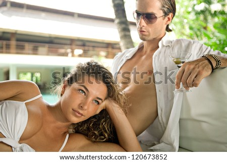 Fashionable sexy young couple lounging on an outdoors tropical bed in an exotic hotel spa garden, relaxing together.