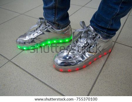 Fashionable sneakers with LED lighting on the legs of a man