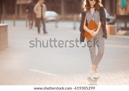 Shutterstock Fashionable spring woman look with black and white striped overalls,sneakers,leather jacket. Girl in sunglasses after shopping, walking, posing at street with red handbag in hands. Concept of fashion.