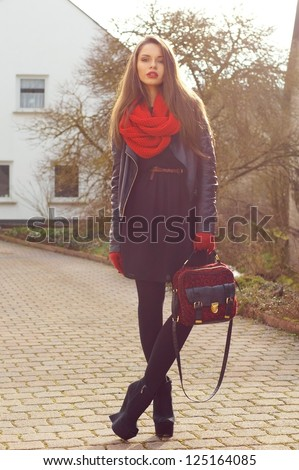 fashionable stylish girl in black dress and leather jacket with red bag