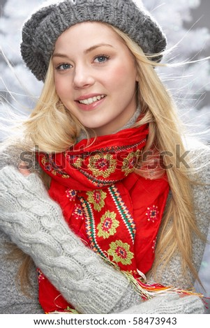 Fashionable Teenage Girl Wearing Cap And Knitwear In Studio In Front Of Christmas Tree