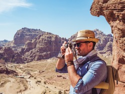 Fashionable tourist with a vintage camera, photographing the main attraction of the city of Petra in Jordan. Colorful photo. Concept of leisure, vacation and travel
