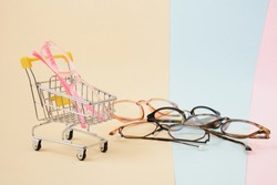 fashionable trendy eyes glasses for correction of vision in a shopping trolley on a colorful background, geometric background from paper of pastel colors, pink beige and light blue