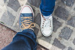 Fashionable unisex canvas shoes standing one next to another - Feet with white and blue used sneakers for girls and boys standing on paved sidewalk