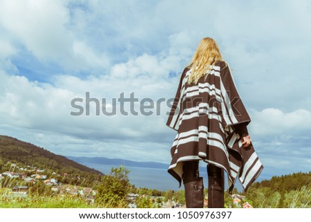 Fashionable, Viking-like Nordic woman with long blonde hair standing on a hilltop looking over the town, shot in Trondheim, Norway, Europe