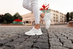 Fashionable white sneakers on female legs, close-up.