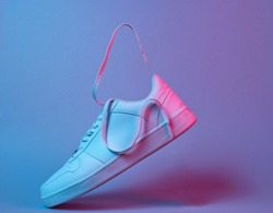 Fashionable white sneakers with flying laces, retro futurism red blue neon light, minimalism