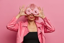 Fashionable woman has pink hairstyle, covers eyes with two delicious doughnuts, has fun and eats junk food, wears stylish jacket, poses over rosy wall. Tasty dessert. Going to eat appetizing food