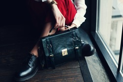 Fashionable woman holding leather green bag. Elegant outfit. Close up of purse in hands of stylish lady. Model posing near the window. Without face. Female fashion. City lifestyle.