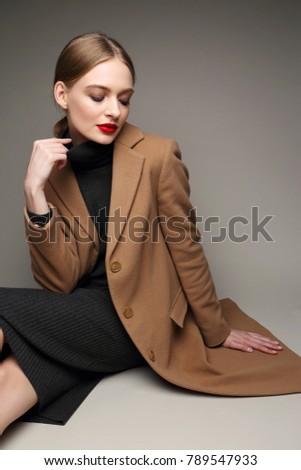 Fashionable woman in a coat. Retro style, black dress, studio shot