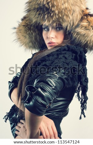Fashionable woman in a fur hat and a leather jacket. Winter style.