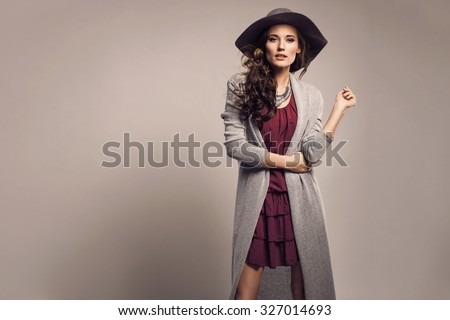Fashionable woman in a hat, dress and long grey sweater, accessories, high heels, posing in studio. Fashion autumn photo #327014693