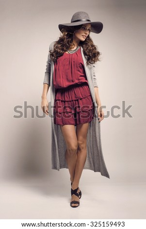 Fashionable woman in a hat, dress and long grey sweater, posing in studio. Fashion autumn photo