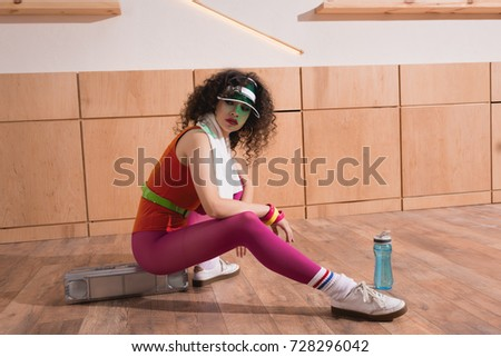 fashionable woman in bright body suit with towel sitting on boombox