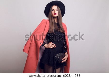 Fashionable woman in pink  coat and black hat posing in studio, looking at camera. cold season. Autumn or winter look.