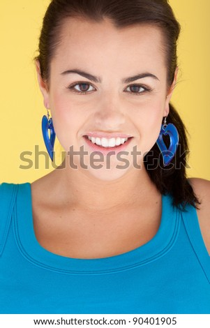 Fashionable Woman In Turquoise with matching large heart earrings and blouse, head and shoulders cropped.