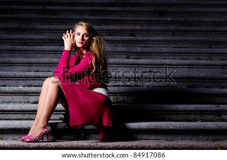 fashionable woman is sitting on stairs at evening