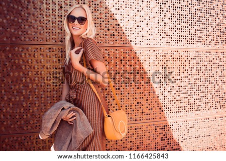 Fashionable woman walking in the street, wearing sunglasses, nice dress, high heels boots, handbag. Fashion urban autumn photo.