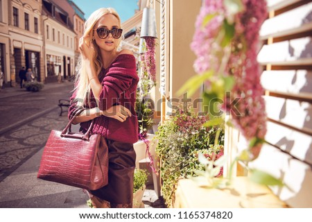 Fashionable woman walking in the street, wearing sunglasses, nice leather skirt, purple sweater, high heels boots, handbag. Fashion urban autumn photo.