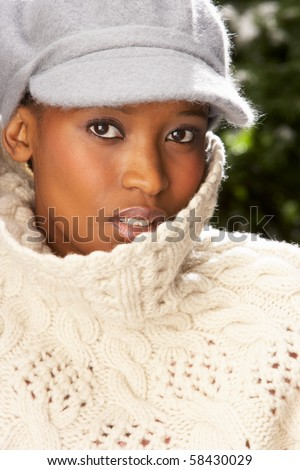 Fashionable Woman Wearing Knitwear And Cap In Studio In Front Of Christmas Tree
